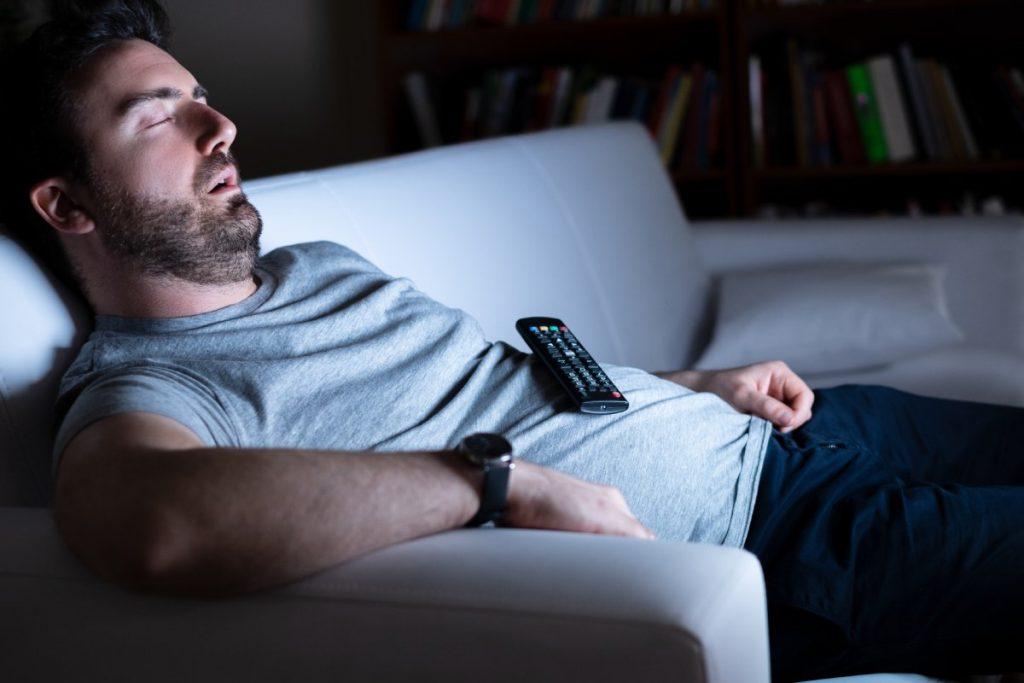 uomo dorme davanti alla tv dopo una giornata pesante