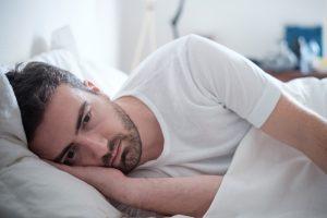 uomo a letto, stanco e depresso, perché da un po' di tempo dorme solo un'ora a notte